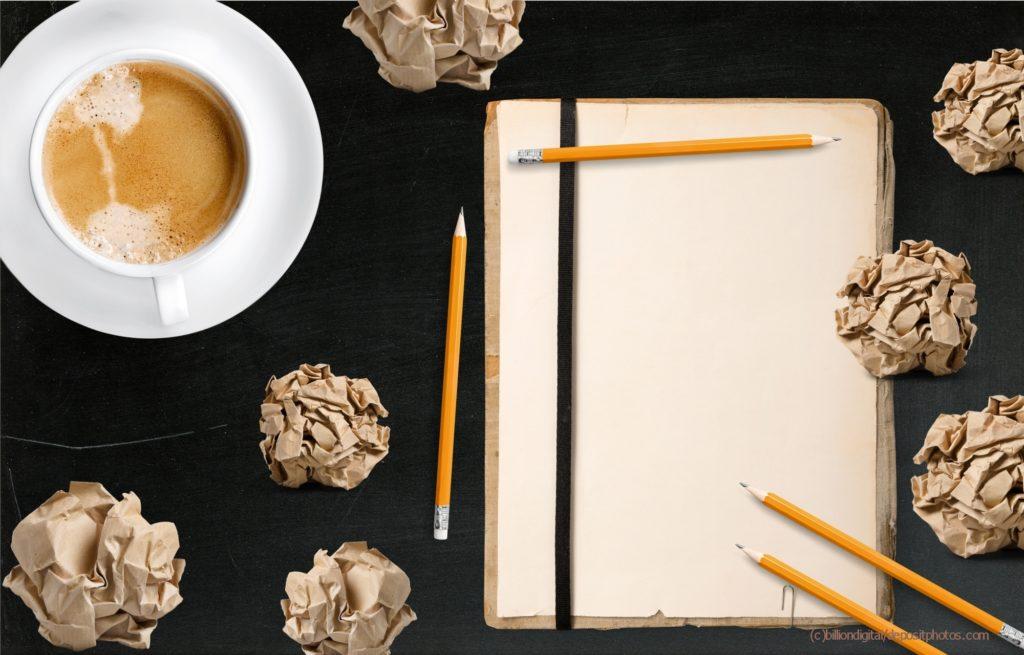 Schreibblock mit zerknülltem Papier und Kaffeetasse